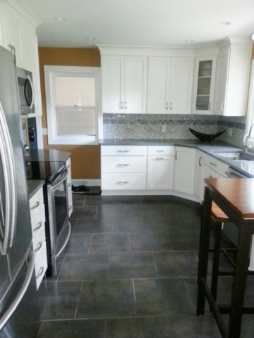 White kitchen cabinets with caramel color walls and porcelain floor.